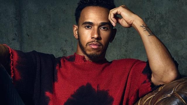 Lewis Hamilton in Model-Pose auf einem braunen Ledersessel.