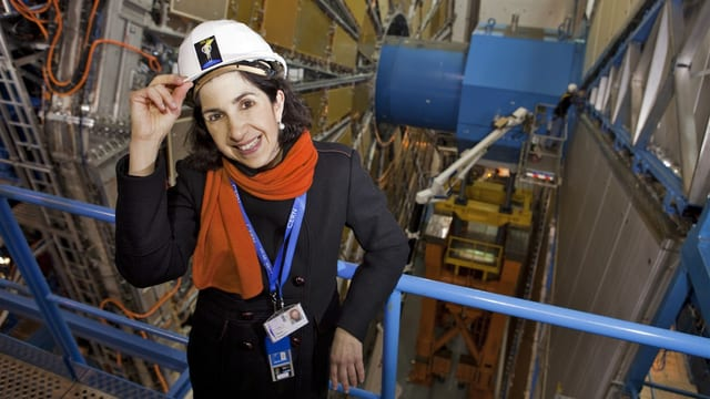 Fabiola Gianotti steht lächelnd in der Kaverne des grossen Detektors Atlas am Cern. Eine Hand hebt sie zum Helm.