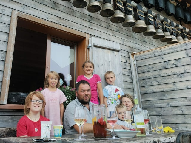 Eine Familie mit fünf Kindern sitzt vor einer Alphütte.