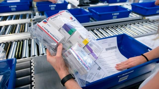 Eine Mitarbeiterin der Versandapotheke Zur Rose kontrolliert im Logistikzentrum in Frauenfeld anhand einer Liste eine Bestellung. (keystone)