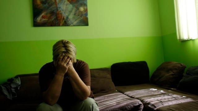 Eine Frau weint im Wohnzimmer.