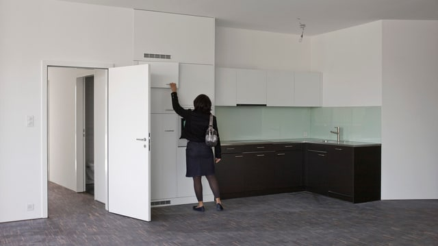Frau besichtigt neue Wohnung. STeht in Küche.