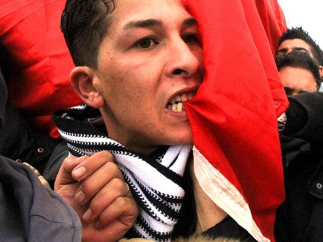 Ein junger Mann beisst in die tunesische Nationalflagge.