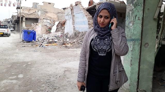 Frau am Handy vor zerstörten Häusern