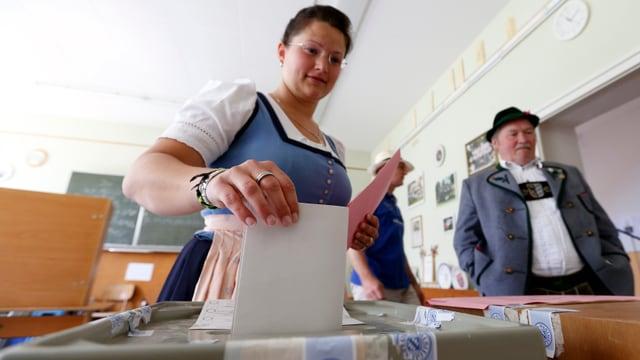 Frau wirft Wahlzettel in eine Urne