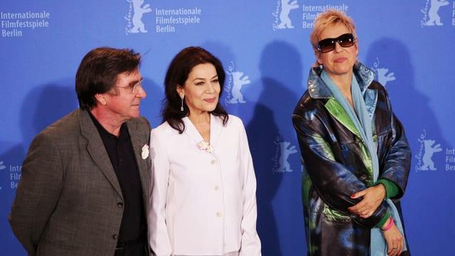 Ein älteter Mann und zwei Frauen stehen vor einer Wand mit dem Berlinale-Logo.