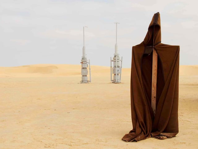 Langer Mantel auf einer Stange, im Hintergrund Antennen.