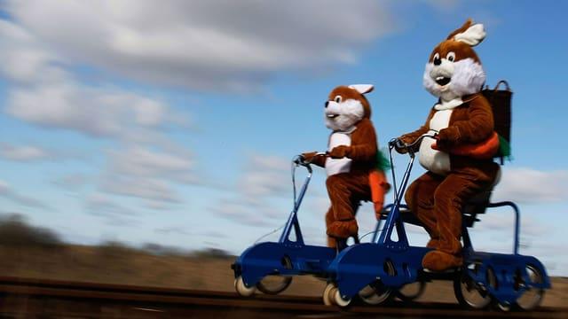 Zwei Menschen in Osterhasenkostüm fahren auf einer Draisine.