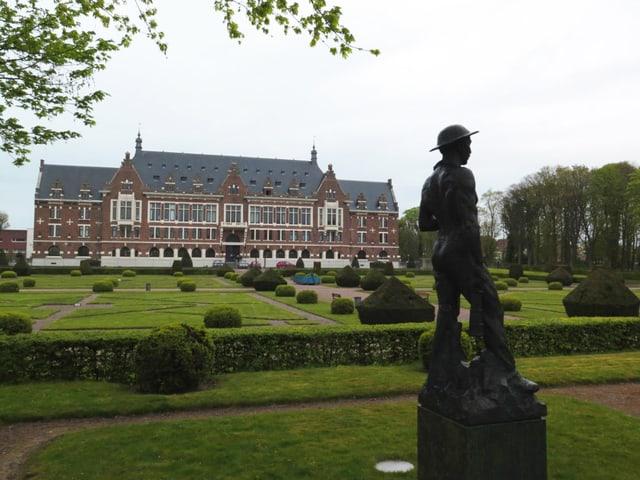 Parkanlage mit Bergarbeiter Statue in Lens, im Hintergrund steht ein grosses Gebäude.