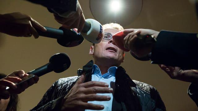 Roger Köppel umringt von Journalisten.