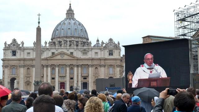 Auf dem St. Petersplatz in Rom steht eine Leinwand, auf der Papst Franziskus zu Pilgern spricht.