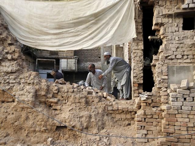 Männer stehen vor einem zerstörten Haus
