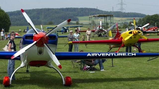 Mehrere Akrobatikflugzeuge mit ihren grossen Propellern stehen auf der Graspiste.