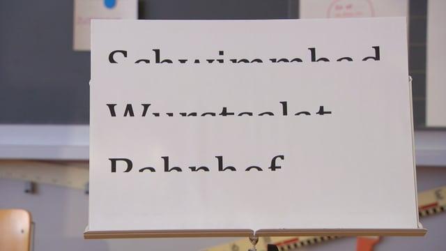 Ein Blatt mit drei horizontal halbierten Wörtern: Schwimmbad, Wurstsalat und Bahnhof