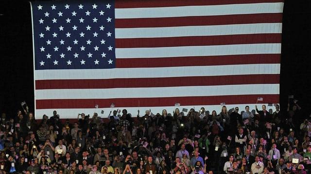 Wahlkampfveranstaltung mit US-Fahne im Hintergrund.