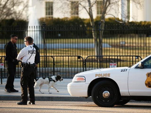 Ein Mann und ein Polizeiauto auf einer Strasse vor einem umzäunten Rasenstück