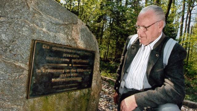 """Salterberg kniet neben einem Stein mit der Auffschrift """"In Erinnerung an den Widerstand gegen den Nationalsozialismus""""."""