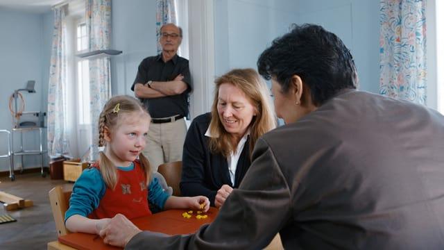 Mara macht eine Übung, bei der sie nur eine Hand benutzen darf, im Hintergrund Remo Largo (Abteilung Entwicklungspädiatrie Kinderspital Zürich)