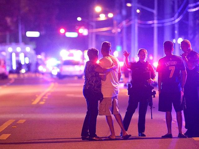 Uniformierte Polizistin mit Zivilisten sprechend. Im Hintergrund stehen Fahrzeuge auf der Strasse