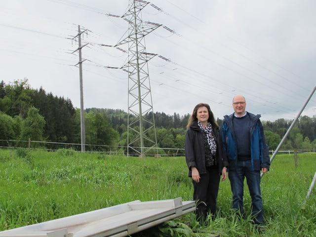 Zwei Personen vor grüner Wiese.