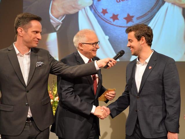 Adrian Küpfer hält Kevin Hirt das Mikrofon hin und Ruedi Matter gratuliert dem Preisträger.