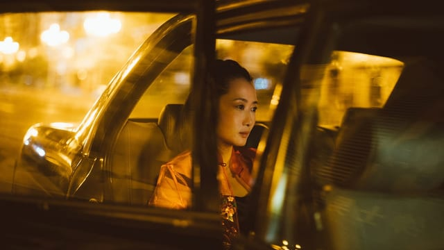 Eine Frau sitzt in einem Auto. Es ist Nacht.