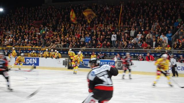 Im Vordergrund Eishockey-Spieler, dahinter viele Zuschauer.
