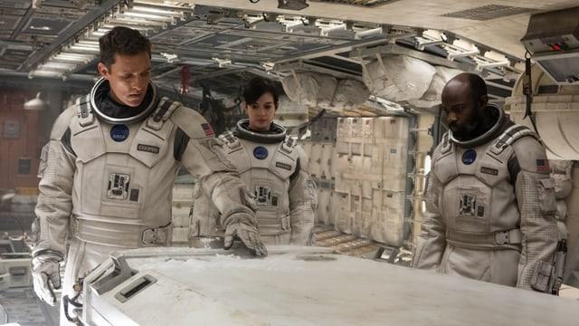 Drei Astronauten in einem Raumschiff.