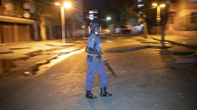 Ein Polizist mit Gewehr steht in einer leeren Strasse in Johannesburg, um die Ausgangssperre während des 2. Lockdowns zu kontrollieren.