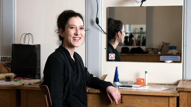 Ariane von Graffenried sitzt lachend an einem Tisch.