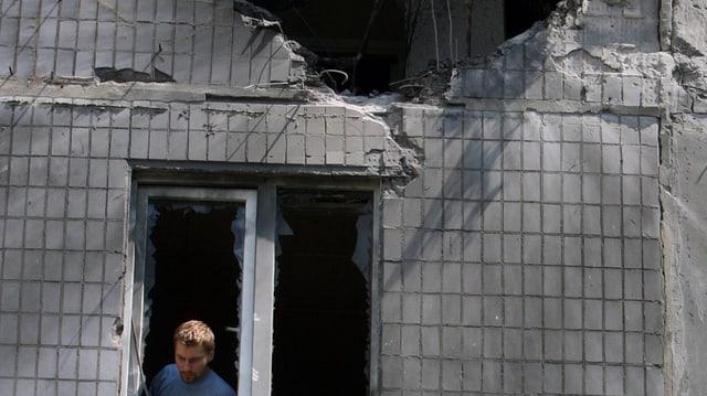 Mann schaut aus dem Fenster eines beschädigten Wohnhauses in Donezk