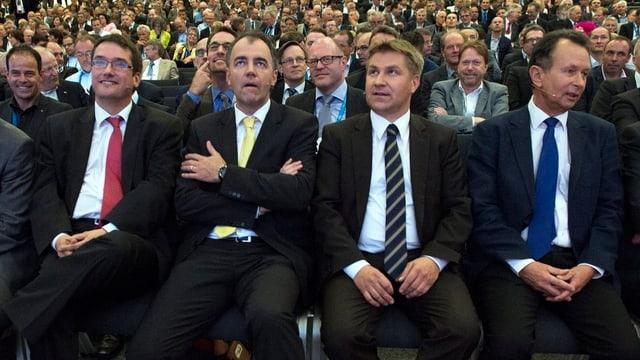 Die vier Herren sitzen – alle in Anzügen und mit Krawatten – in der vordersten Reihe des Publikums.