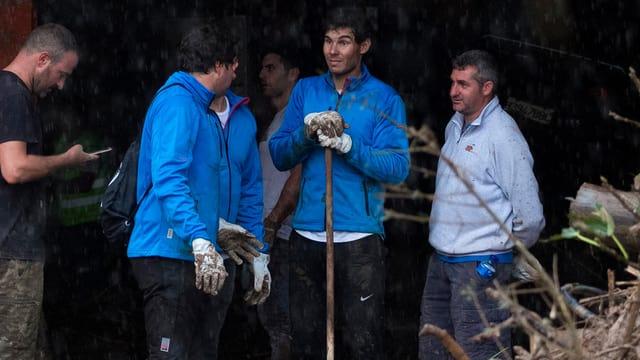 Rafael Nadal mit einer Schaufel in der Hand im Gespräch mit weiteren Helfern in Sant Llorenc.