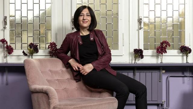 Eine Frau sitzt auf der Lehne eines Sofastuhls.