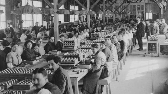 Fabrikhalle, Männer und Frauen, Munitionskisten, hochstehende Granaten