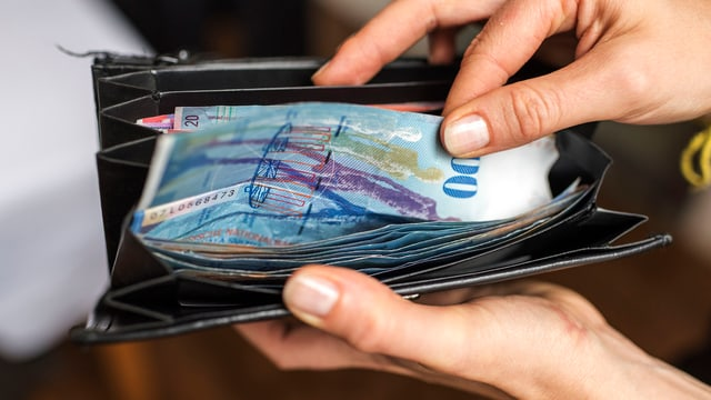 Hand ergreift in Portemonnaie einen 100-Franken-Schein.