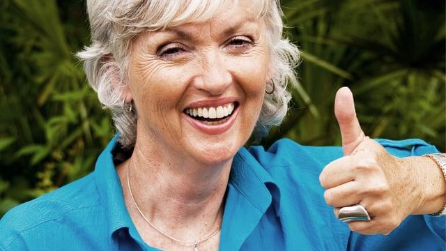 Lachende Seniorin im blauen Hemd hebt den Daumen