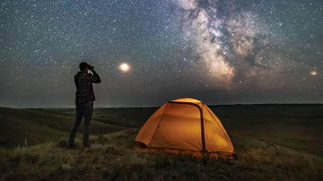 Ein Mann steht neben einem Zelt und schaut auf den klaren Sternenhimmel.