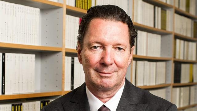Martin Suter in Porträtansicht. Er steht vor einem grossen Bücherregal und blickt in die Kamera.