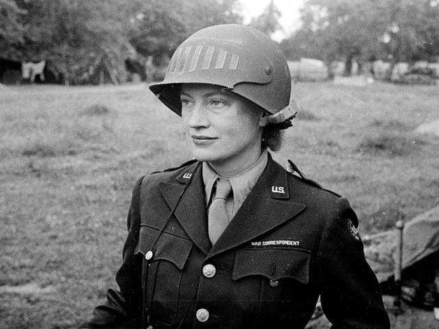 Eie junge Frau mit Militäruniform und Helm blickt geradeaus.
