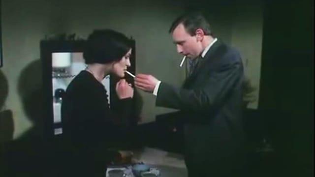 Ein Mann mit Zigarette im Mund gibt einer Frau Feuer.