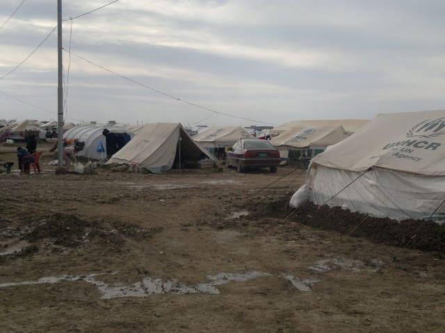 Matschiger, nasser Boden im Flüchtlingslager. Dahinter Zelte.