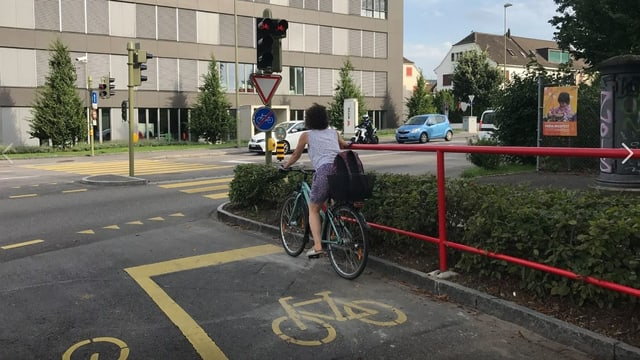 Eine Frau auf dem Fahrrad hält sich am Geländer.