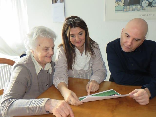 Maria Infantino, Daniela Infantino und Daniel Nellen schauen ein Bild an.