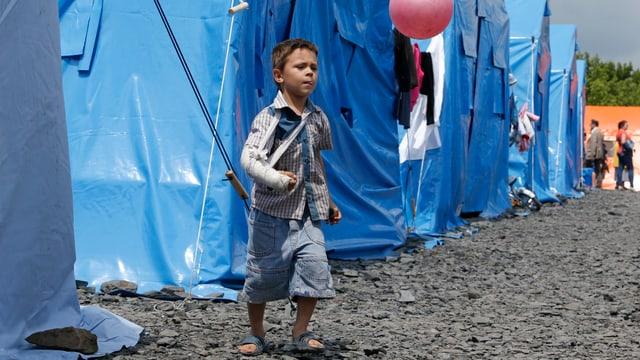 Ein Junge mit spielt mit einem rosaroten Ball zwischen blauen Zelten in einem Auffanglager.