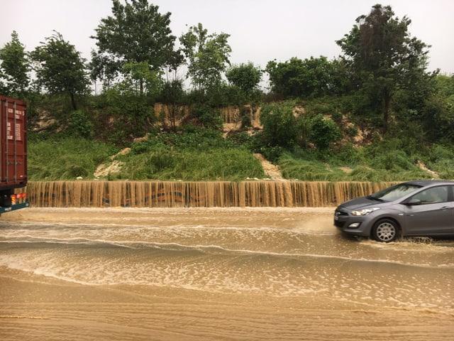 Wasser auf Strasse und Autos, die versuchen, das Wasser zu queren.