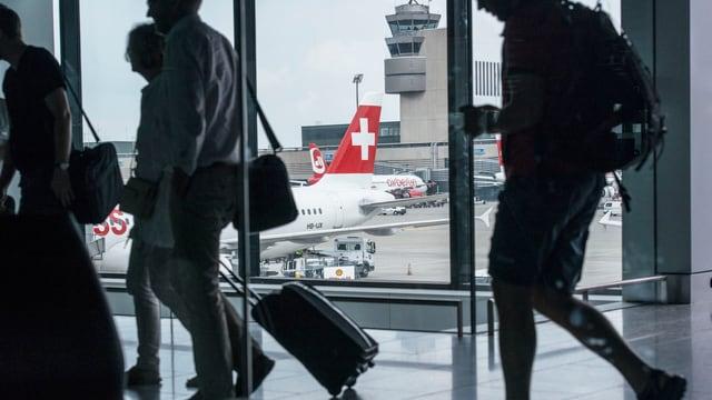 Passagiere gehen einen Gang entlang, durch die Scheibe sieht man den Tower des Flughafens Zürich und eine Swiss-Maschine.