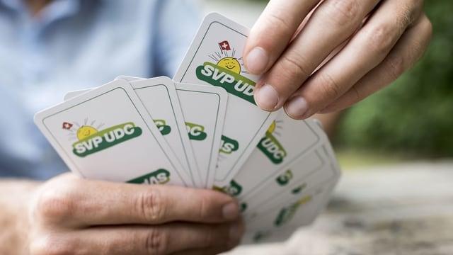 Ein Mann hält ein Kartenspiel mit SVP-Logo in den Händen