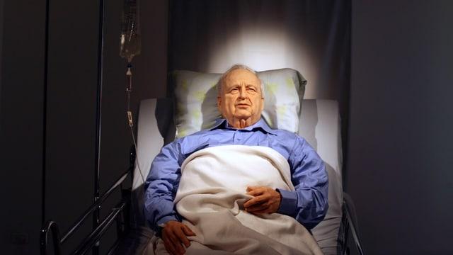Wachsfigur im Bett mit blauem Nachthemd.