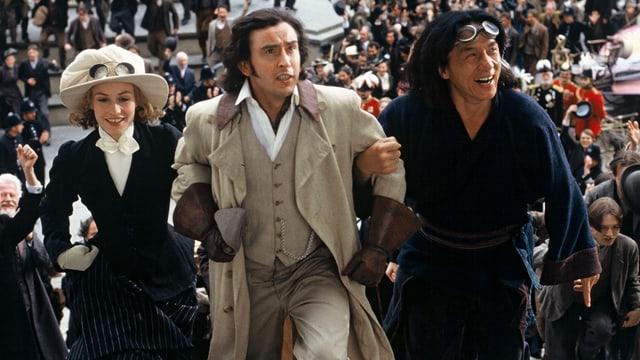 Eine europäische Frau und ein Mann und ein chinesischer Mann rennen Arm in Arm. Im Hintergrund ist eine Menschenmenge zu erkennen.